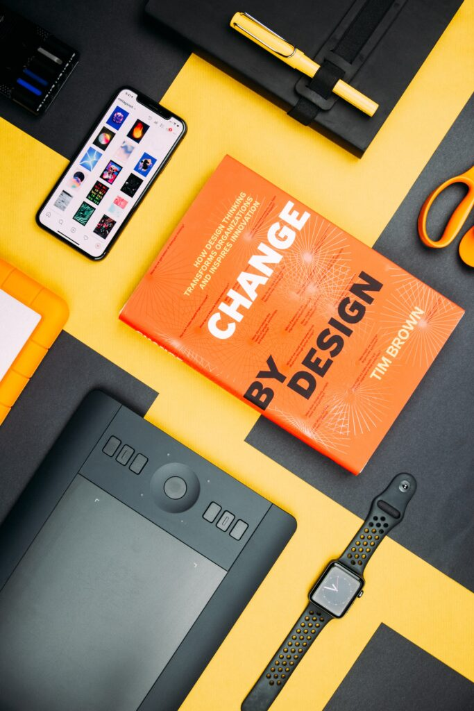 a book about design in a desk with other gadgets