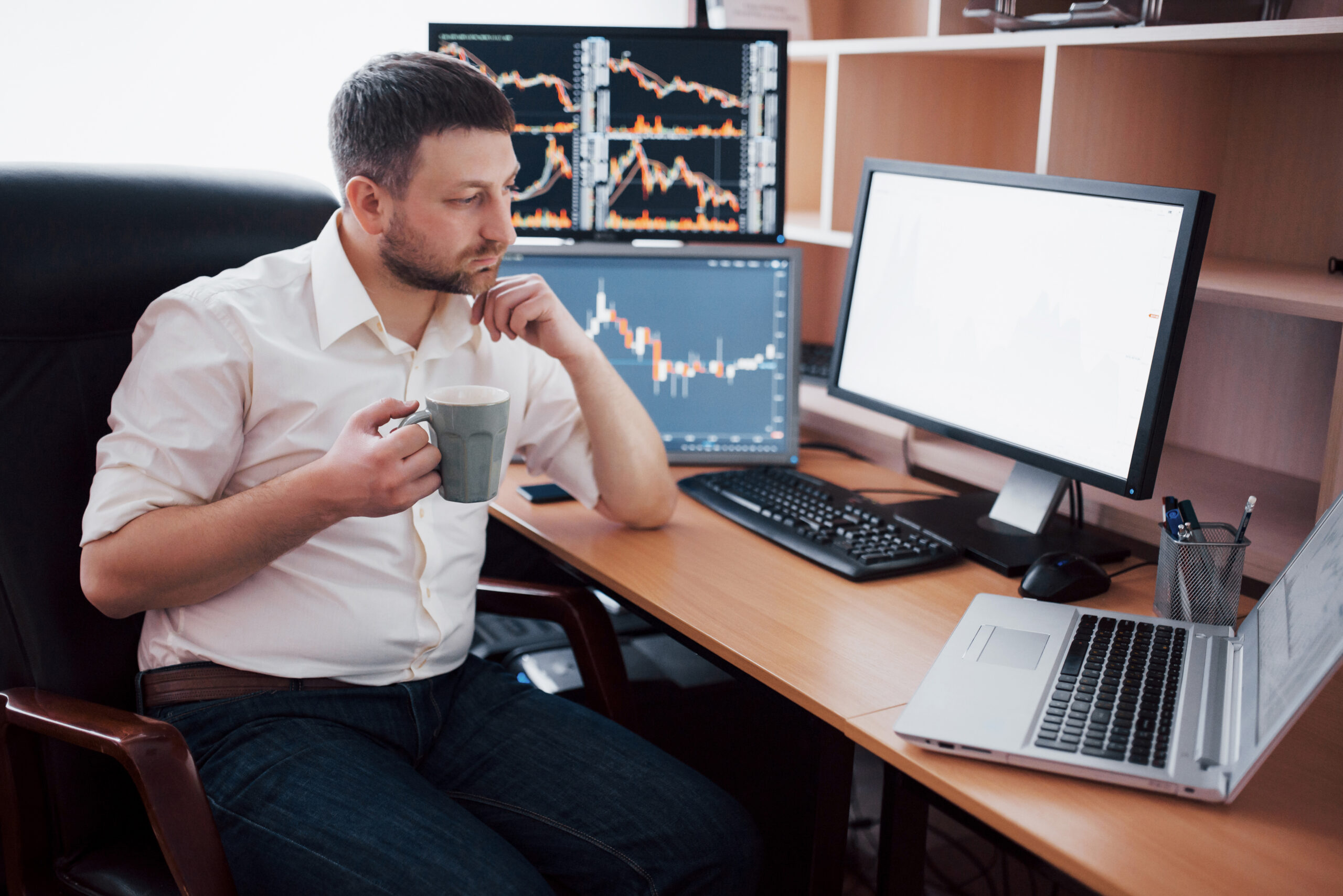 Young businessman is sitting in office at table, working on computer with many monitors,diagrams on monitor.